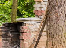 Closeup of old red brick outside fireplace. Red brick outside fireplace with a shovel leaning against a tree and green foliage in the background Stock Image