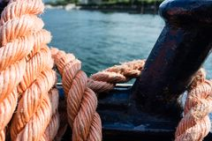 Closeup of an old red frayed boat rope, water background with landscape Royalty Free Stock Image