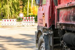 Closeup of old rusty and dirty red truck side, paint peeling on cargo area wall, large tires visible, blurred road block sign and. Closed path in background royalty free stock photo