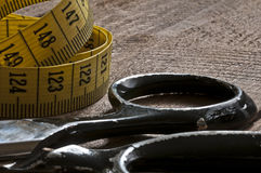 Closeup of old Scissors and measure tape on wood Stock Photos
