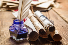 Closeup of old scrolls and blue ink in the inkwell Stock Photos