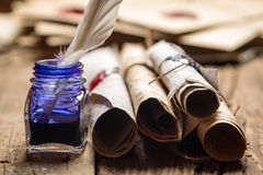 Closeup of old scrolls and blue ink in the inkwell Royalty Free Stock Images