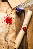 Closeup of old scrolls,  sealing wax and blue ink. On wooden table Stock Images