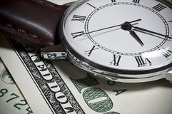 Closeup of old watch on one hundred dollar bill. A DLSR photo of old hand watch on hundred dollar bills Royalty Free Stock Images