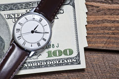 Closeup of old watch on one hundred dollar bill. A DLSR photo of old hand watch on hundred dollar bills on wooden table Stock Image
