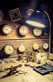 Old watchmakers workshop full of clocks and tools. Closeup of old watchmakers workshop full of clocks and tools royalty free stock images