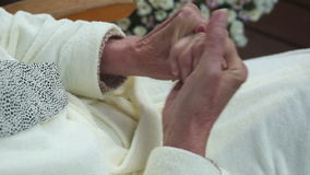 Closeup of old woman's hands applying lotion