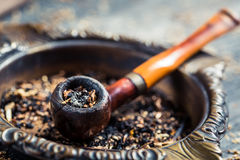 Closeup of old wooden pipe in an ashtray Royalty Free Stock Image