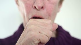 Closeup of older woman coughing