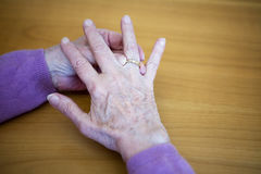 Closeup of older woman hands putting ring on her finger Royalty Free Stock Photography