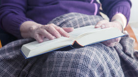 Closeup of older woman sitting by window and reading a book Stock Image