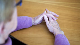Closeup of older womans hands resting on table royalty free stock photo