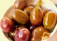 Closeup of olives pickled in oil. Macro of pickled olives in a bowl royalty free stock photography