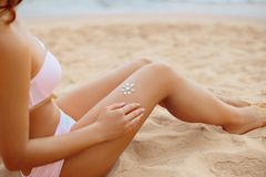 Closeup On Female Hand Applying Sunscreen Creme On Beautiful Legs. Skincare. Royalty Free Stock Photography