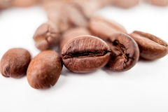 Closeup on one coffee bean isolated on blur roasted beans background. Macro grain coffee black espresso. Royalty Free Stock Photography