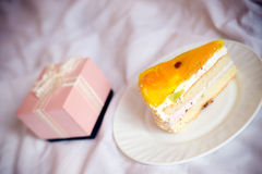 Closeup on one great pink box of present or gift and delicious slice of cake on a plate on the white background. Pink box of present or gift and delicious slice royalty free stock images
