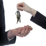 Closeup of one hand with key ring hands over keys to other hand Stock Image