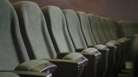 Closeup one Row of Empty Gray Chair in Dark Cinema Hall stock video