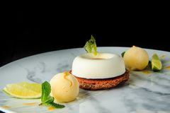 Closeup one shortbread cookie with white mousse cream. Served with two spheres of ice cream and sliced limes royalty free stock photography