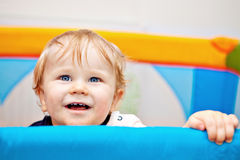 Closeup of one year baby boy. 11 months Baby boy reaching out of his bed holding the edge with hands and laughing Stock Image