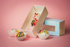 Closeup of open box with homemade cake balls with colorful sprin. Closeup photo of open box with homemade cake balls with colorful sprinkles over pink background Royalty Free Stock Photography
