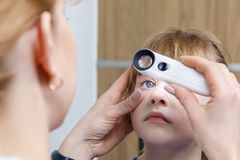 A closeup of an ophthalmologist checking the eye of a child stock photos