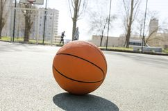 Closeup of orange ball for basketball on the rubber sport court.Sport ground outdoor in the yard. School sport ground outdoor.Basketball ball on the empty sport royalty free stock photos