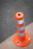 Closeup orange bollard on pavement Stock Photos