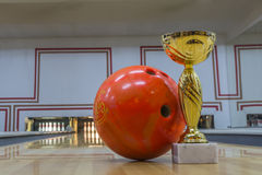 Closeup of orange bowling ball near golden trophy Royalty Free Stock Photos