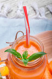 Closeup of an orange carrot smoothie in a mason jar with sappy green leaves of mint on a light blurred background. Close-up of a fresh carrot, a mason jar with Stock Photo
