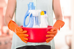 Closeup orange gloves holding red bucket of cleaning products and smiling to camera, housecleaning concept stock images