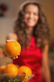 Closeup on orange in hand of young housewife in kitchen Stock Photos