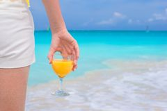 Closeup orange juice in a female hand on background of the sea Stock Photos