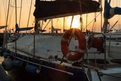 Closeup of Orange Lifebuoy and Rolled Rope on Sailing Boat Stock Image