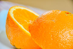 Closeup of orange sliced in half. Macro shot of sliced orange on a white plate with a colorful tablecover Royalty Free Stock Photography