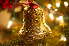 A closeup of an ornate gold bell Christmas ornament. A closeup of an ornate gold bell Christmas ornament hanging on a fur tree with lights in the background stock images