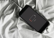 Closeup of out of battery mobile phone charging and lying on white fabric background stock photos