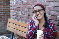 Closeup outdoor portrait of cute happy brunette ethnic teenage girl with takeaway coffee talking on smartphone.  Royalty Free Stock Photography