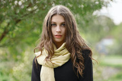 Closeup outdoor portrait of young beautiful brunette woman with wavy long hair looking into camera posing against forest park back. Closeup outdoor portrait of Royalty Free Stock Image
