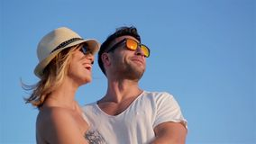 Closeup Outdoors Portrait of Smiling Happy Couple in Fashionable Sunglasses on Blue Sky Background During Sunny Windy stock video footage