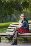 Closeup outdoors portrait of young adorable blonde woman sitting on the park bench  in windy weather conditions with green blurry Stock Photography