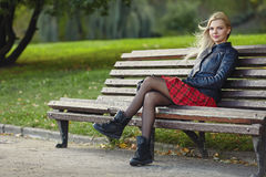 Closeup outdoors portrait of young adorable blonde woman sitting on the park bench  in windy weather conditions with green blurry Royalty Free Stock Images