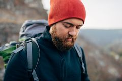 Closeup outdoors portrait of young handsome hiker male hiking in mountains wearing red hat. Traveler bearded man trekking. And mountaineering. Travel, people stock photos