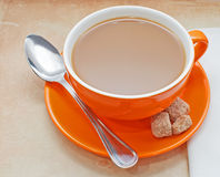 Closeup of orange coffee cup. Closeup overview of orange coffee cup on table top Stock Image