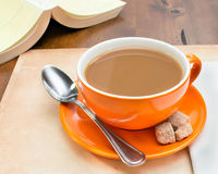 Closeup of orange coffee cup. Closeup overview of orange coffee cup on table top Royalty Free Stock Photo