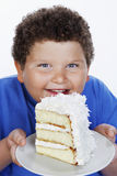 Closeup Of An Overweight Boy Holding Large Slice Of Cake Stock Photos