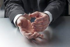 Closeup på affärsmanhänder med handbojor på för begrepp av brottet eller rättvisa på arbete Royaltyfria Bilder