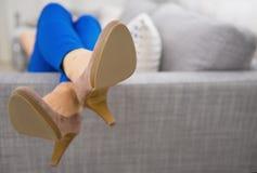 Closeup på ben som lägger på soffakvinna arkivfoto