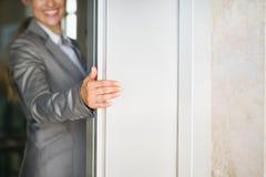 Closeup på dörr för hiss för kvinnahandholding royaltyfri bild