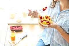 Closeup på den unga hemmafrun som äter sallad för ny frukt arkivbilder